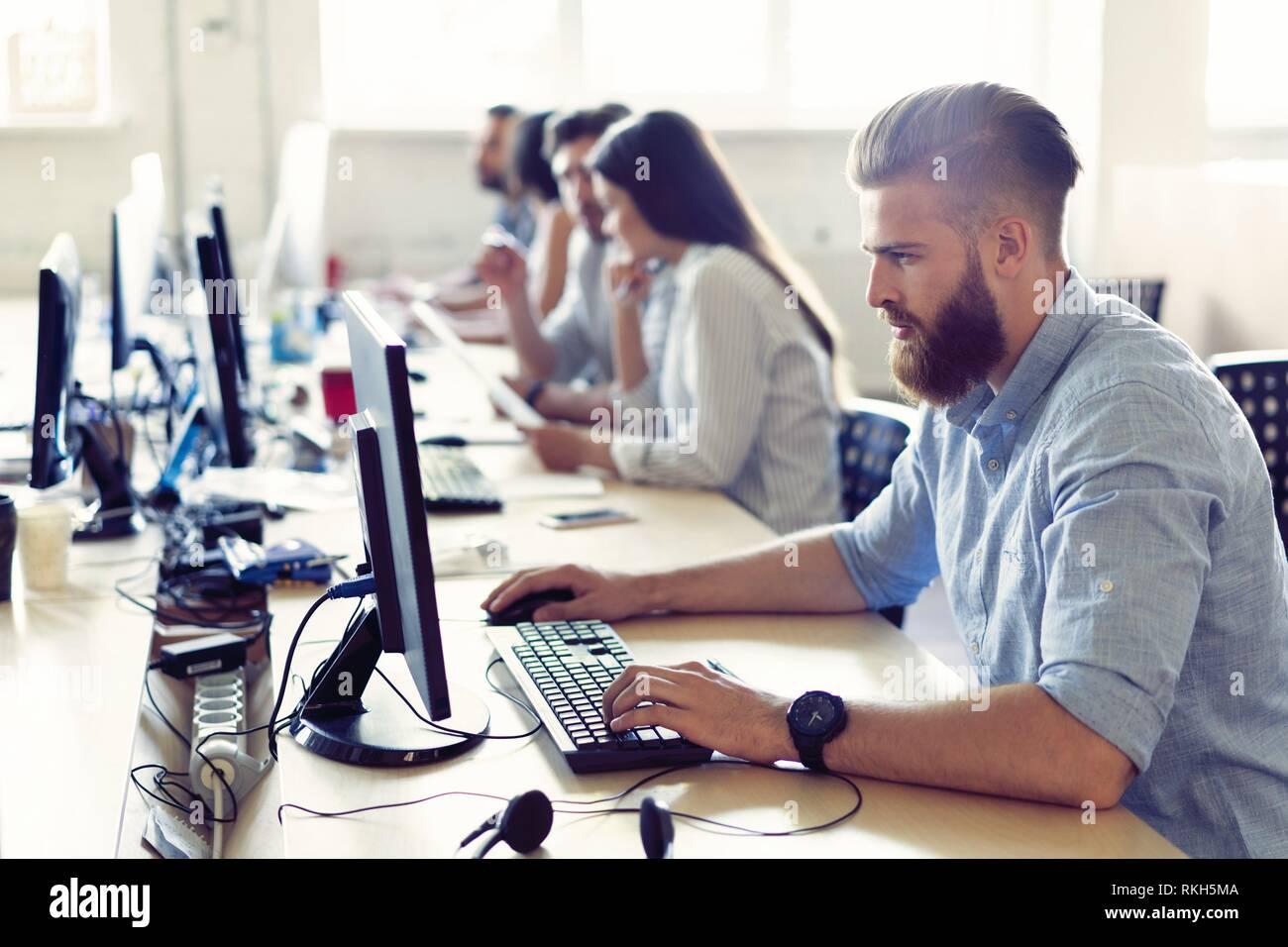 Die Kollegen sind auf ihre Arbeit konzentriert, finden die Lösungen ihrer Unternehmen Probleme, sitzen am Arbeitsplatz in einer Reihe in hellen modernen Büro. Stockfoto
