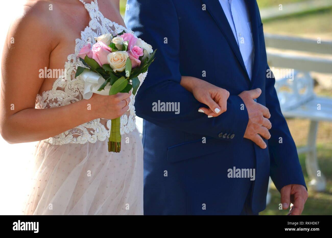 Junge Braut in eine weisse Spitze Neckholder Kleid Hochzeit gehen