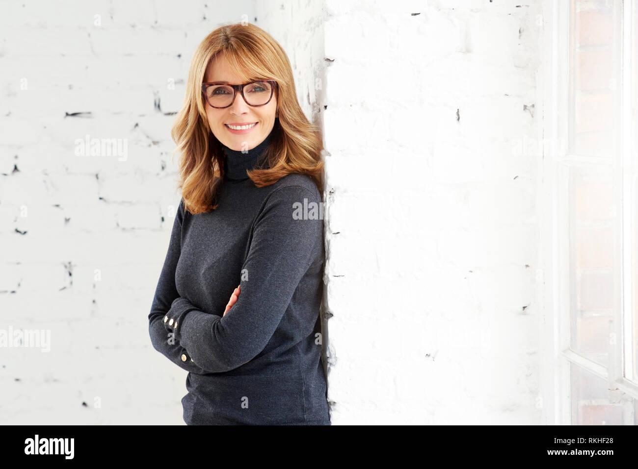 Portrait von attraktiven Frau mittleren Alters tragen Rollkragen Pullover und Jeans beim Entspannen am Fenster und Blick auf Kamera. Stockfoto