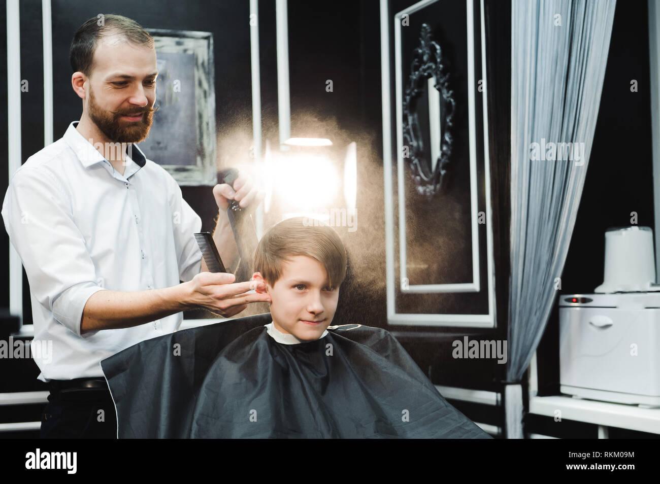 Junge schöne Friseur die Haare schneiden von süßen Jungen in einem