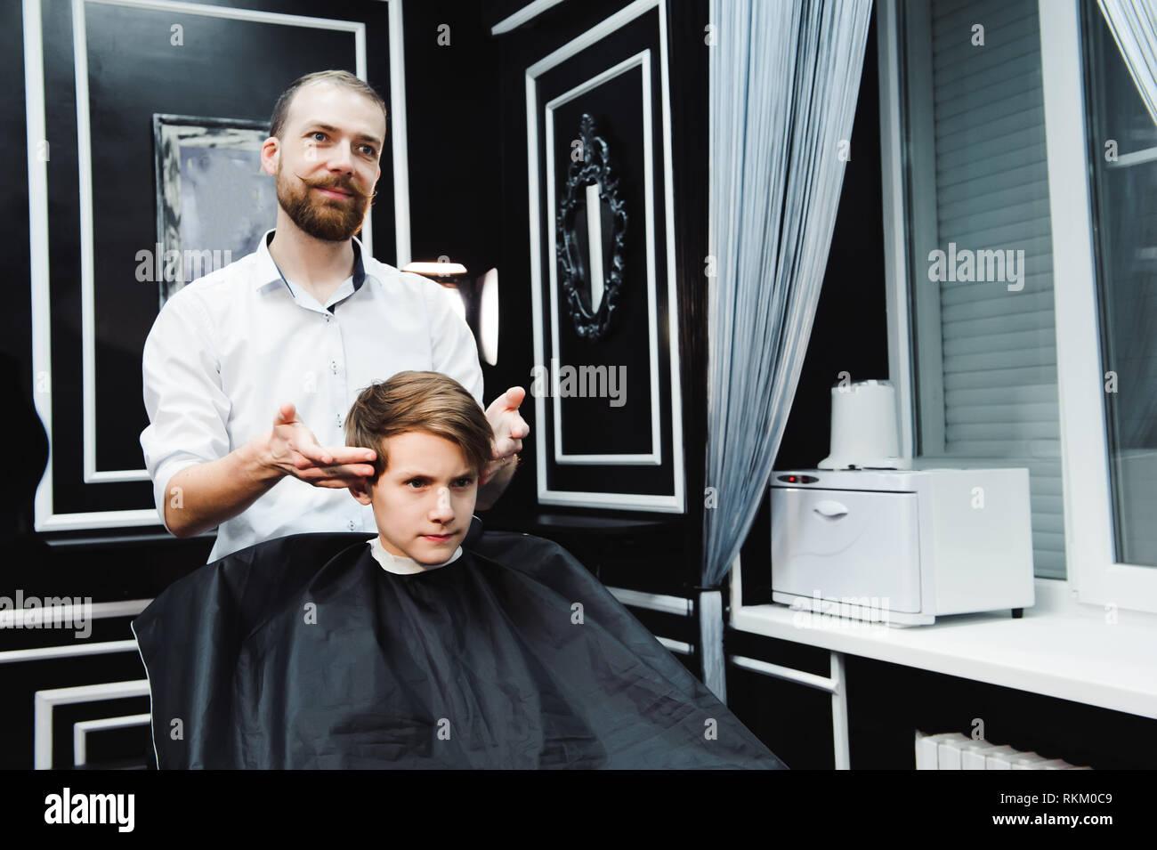 Junge schöne Friseur die Haare schneiden von süßen Jungen im