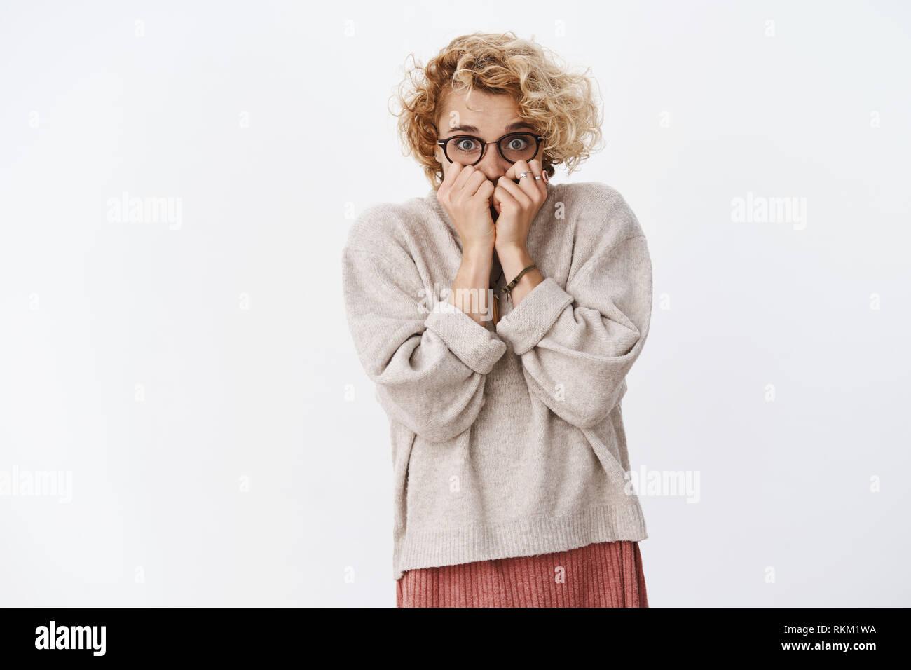 Mädchen verängstigt zitternden schließen Gesicht, Hände halten in der Nähe von Mund zu knallen, die in der Kamera von Horror in Erstarrung über weiße Wand heben Stockbild