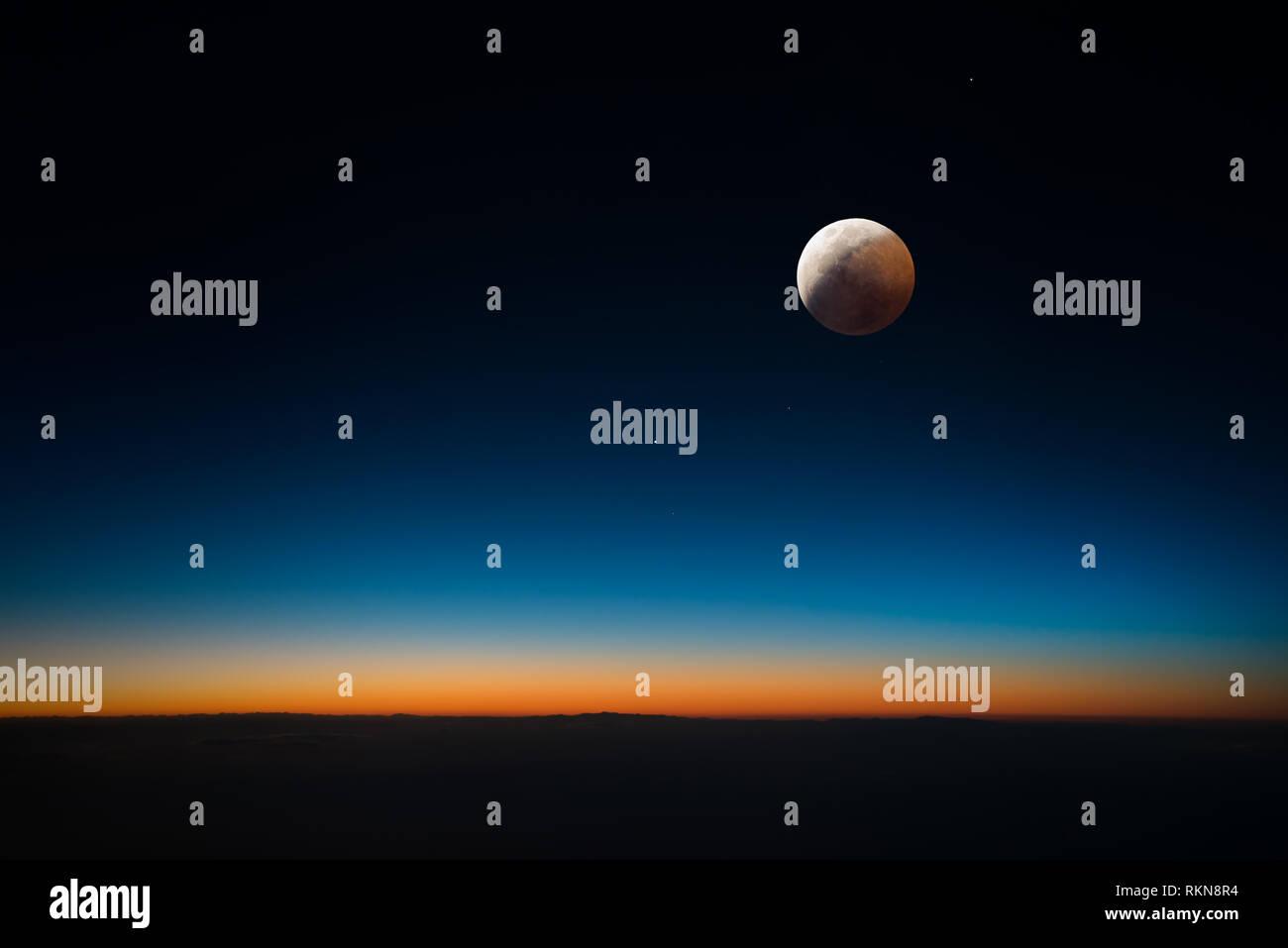 Verfinsterte Mond mit Sonnenlicht verbogen, die durch die von der Atmosphäre der Erde den Mond rot Stockbild