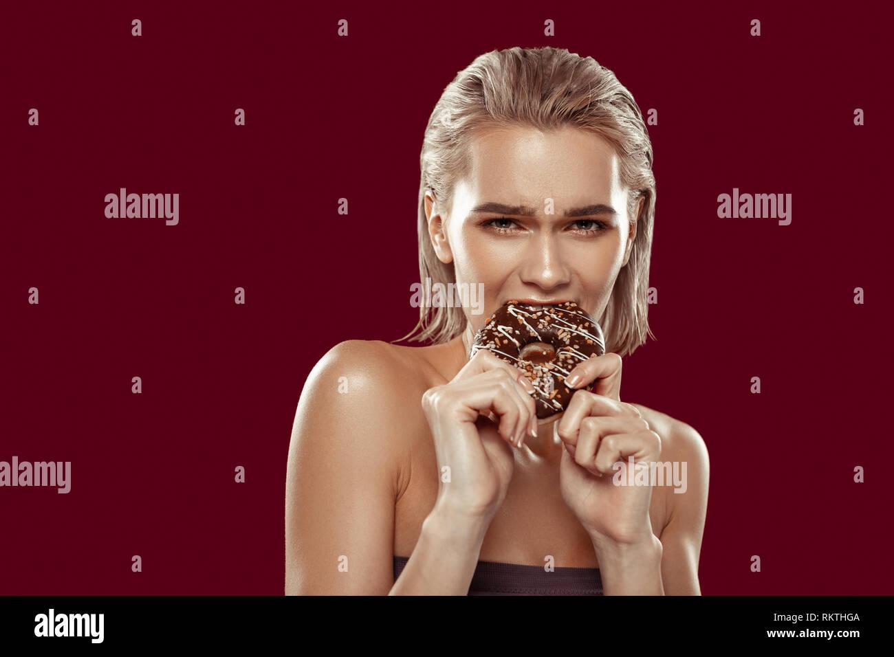 Dark-eyed Frau, die keine Wünsche süße ungesunde Donuts zu essen Stockbild