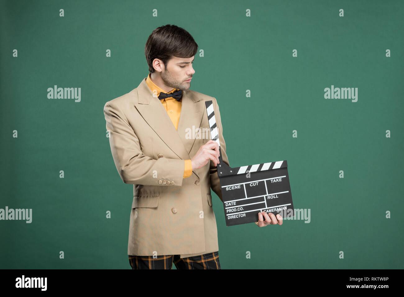 6ebec22d896a31 Schöner Mann in Vintage Kleidung Holding film Klappe isoliert auf Grün