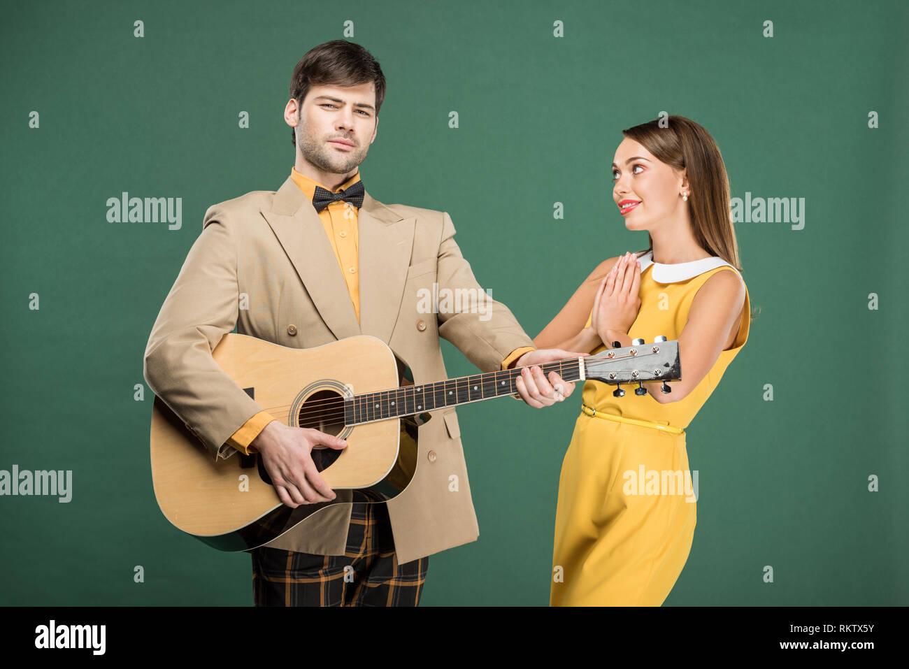 ee3508ae73adae Schöner Mann in Vintage Kleidung spielen akustische Gitarre während schöne  Frau tun bitte Geste isoliert auf Grün