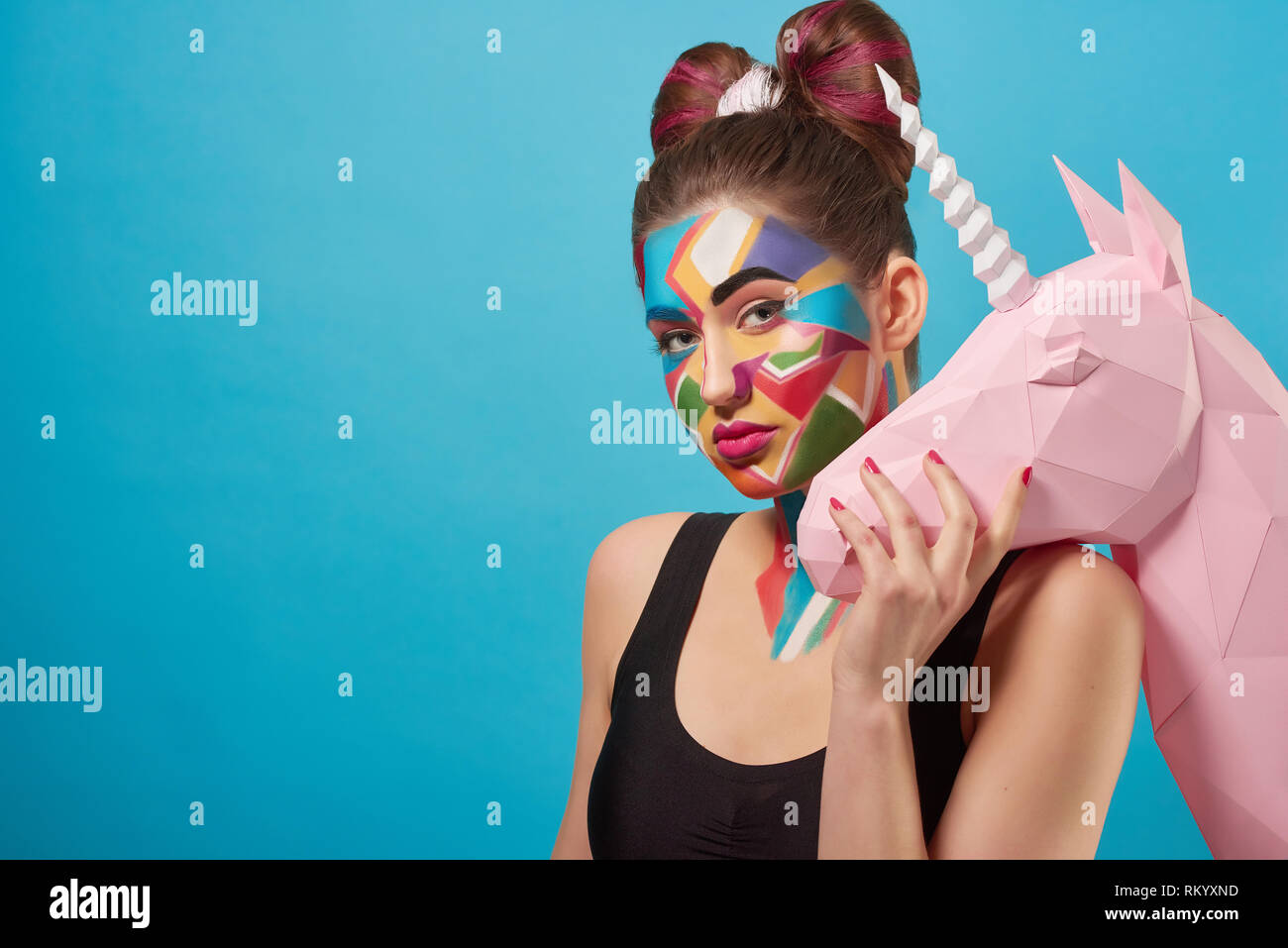 Porträt der Schönen model posing, an der Kamera schaut. Bezaubernde Frau die Hand auf 3D-Papier Einhorn Kopf. Funky girl hat Pop Art kreativ Make-up. Papercraft Konzept. Stockbild