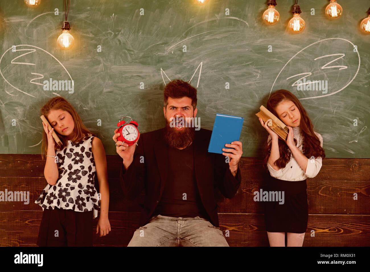Lehrer und Schüler Mädchen im Klassenzimmer, schwarzes Brett für den Hintergrund. Kinder und Lehrer und gezeichnet von Chalk Hörner. Mann mit Bart schreien während Stockbild