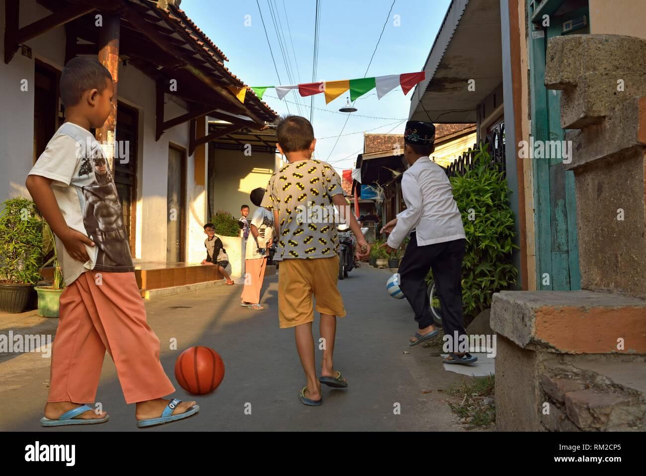 Jungen spielen Ball in einer Straße von Kauman Batik Dorf (Kampung), ist eine kreisfreie Stadt, mit vielen Batik Hersteller und Craftmen, der pekalongan, Java Stockbild