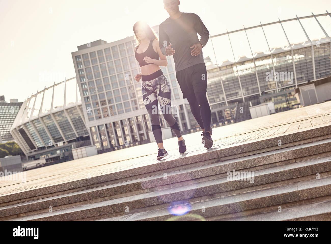0a0e6698ab0bf9 Volle Länge Portrait von sportlich-junge interracial Paare in Sportkleidung  liefen die Treppe in der städtischen Umwelt. Gemeinsame Hobbys. Gesunde  Paare.