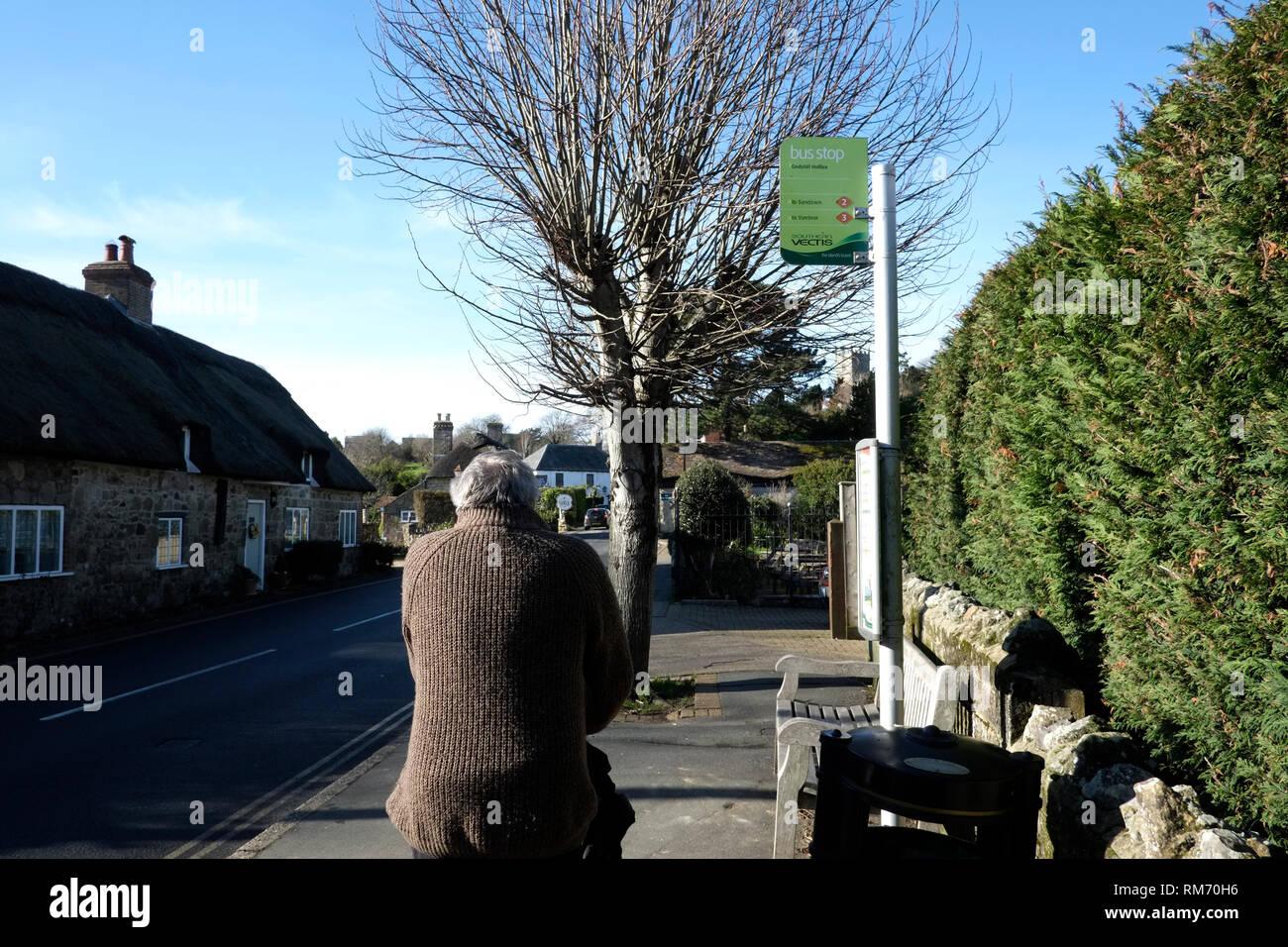 Rentner wartet auf mit dem Bus an der Haltestelle zu gelangen Stockbild