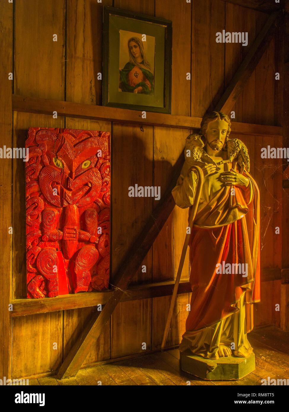 Maori Schnitzereien und die Statue von Christus, dem Guten Hirten, mellow goldenes Licht auf Holz verkleideten Wänden, Kirche, Pepara Koriniti Marae, Whanganui Stockbild