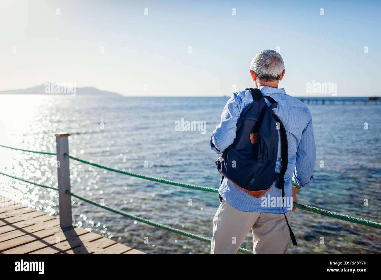 Älterer Mann mit Rucksack Landschaft bewundern, das Rote Meer und die Insel Tiran am Pier. Reisen und Tourismus Konzept. Sommer Urlaub Stockbild