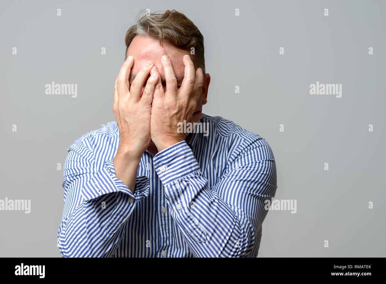 Im mittleren Alter Mann bedeckte sein Gesicht mit den Händen in einer oberen Körper Porträt über einen grauen Hintergrund Stockbild