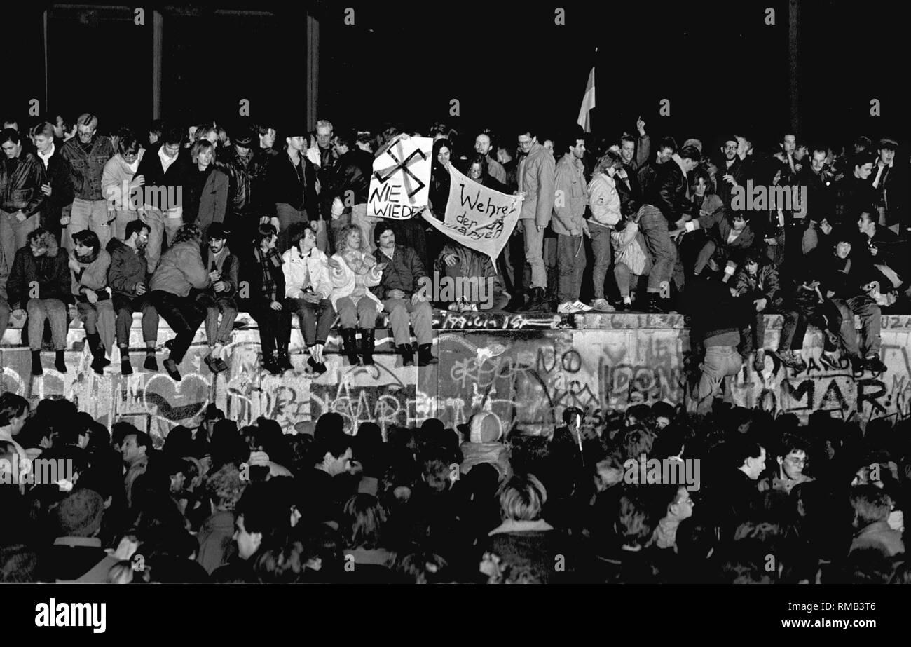 Berlin, 10. November 1989: Tausende Berliner sammeln auf der Berliner Mauer am Brandenburger Tor die Öffnung der Grenze zu feiern. Stockbild