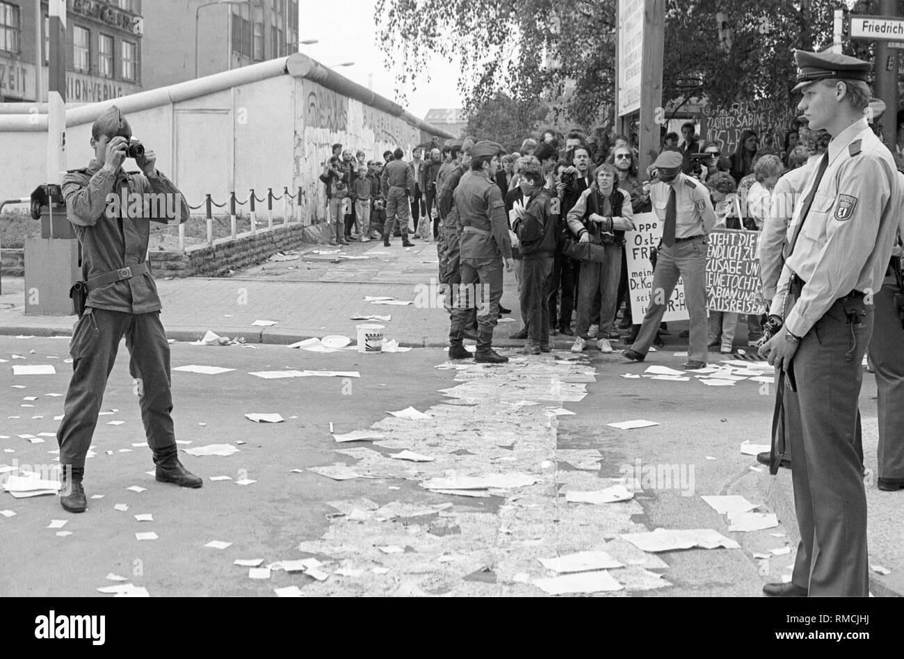 Die Gegner der 1987 Volkszählung stick Zehntausende Anmeldeformulare, die Berliner Mauer während einer spektakulären Kampagne am Grenzübergang Checkpoint Charlie, ein DDR-Grenzsoldaten Fotografien die Szene als die West-Berliner Polizei versucht, die Aktion zu stoppen. Stockfoto