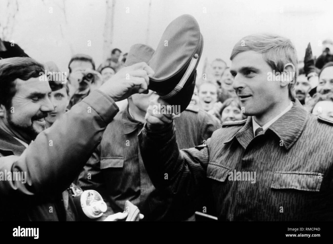West-berliner Polizist und DDR-Grenzsoldaten Soldat in der Menge nach der Maueröffnung. Der Polizist Hände seine Kappe auf der borderman. Stockfoto