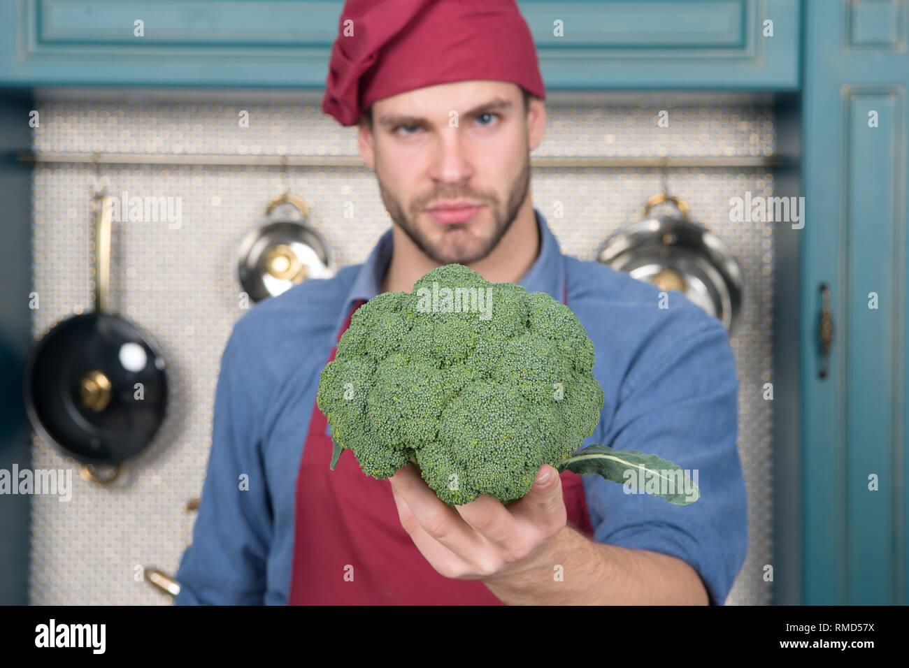 Hauptbestandteil. Denken Sie an Hauptbestandteil natürliches Aroma. Man-Chef hält Brokkoli nachdenkliche Gesicht Defokussierten. Empfehlen die Auswahl der Zutaten ergänzt. Bestandteil in Raw einfach in Erwägung zu ziehen. Stockbild