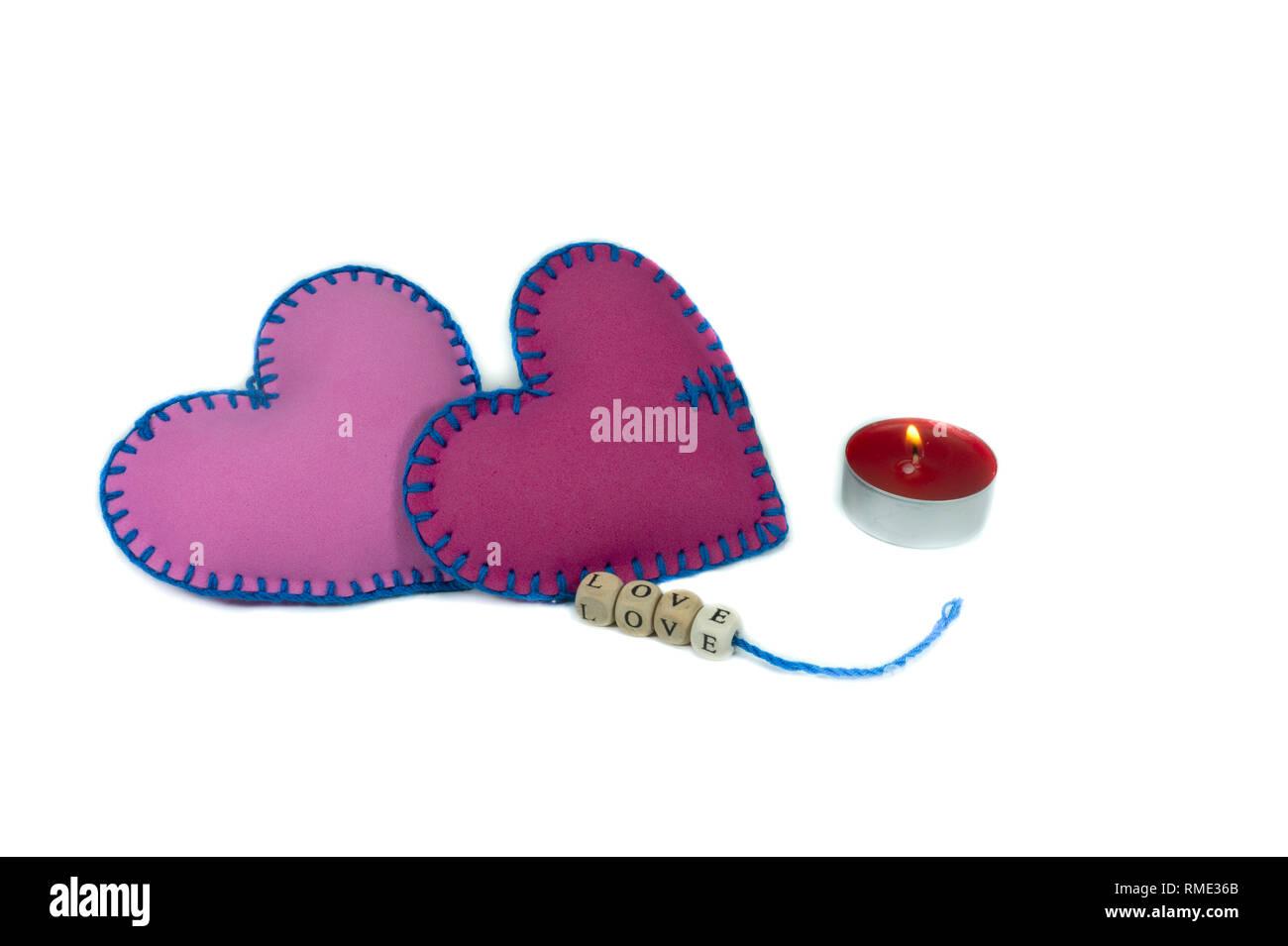 Gebrauchte Textilmaschinen Herzen mit dem Wort Liebe auf Blöcken auf Strings auf weißem Hintergrund für eine romantische Beziehung isoliert mit Gewinde genäht, Valentinstag, Brok Stockfoto