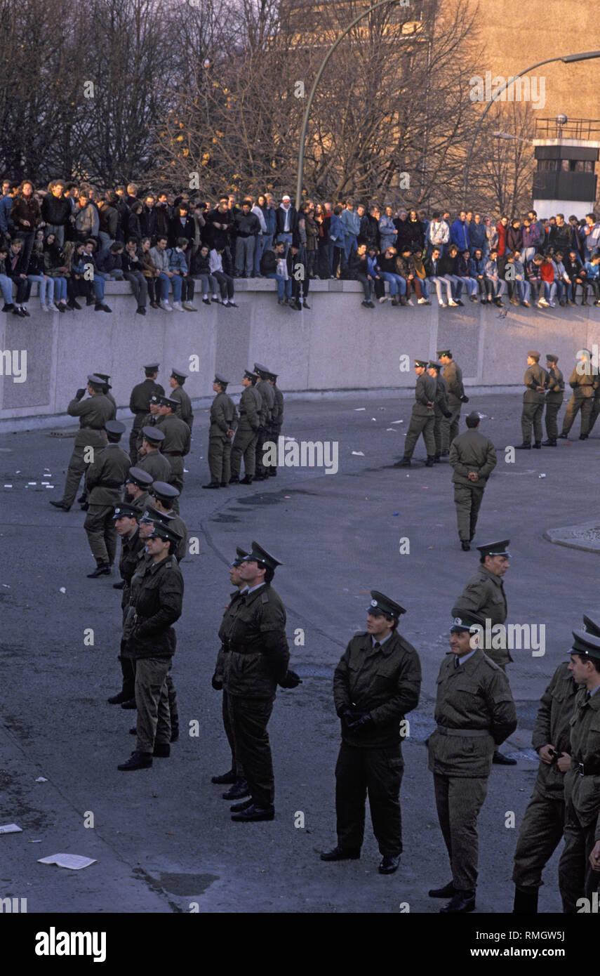 Tausende von Ost und West Berliner feiern die Öffnung der Grenze auf der Berliner Mauer am Brandenburger Tor. Ddr-Grenze wachen Menschen daran hindern, in den geschützten Bereich auf dem Platz vor dem Brandenburger Tor und den Pariser Platz. Stockfoto