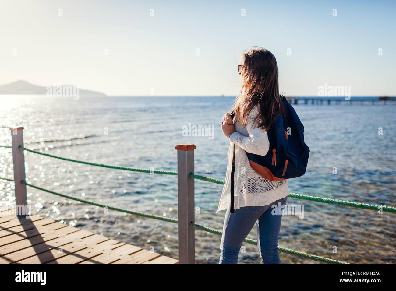 Junge weibliche Touristen mit Rucksack Landschaft bewundern, das Rote Meer und die Insel Tiran zu Fuß auf den Pier. Reisen Konzept. Sommer Urlaub Stockbild