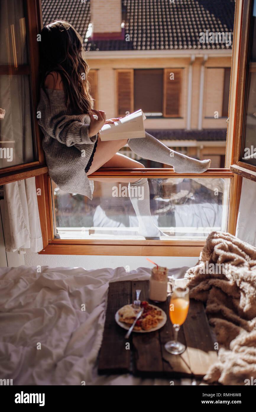 Junge Frau sitzend mit leckeren Drink und Buch über Fenster Stockbild