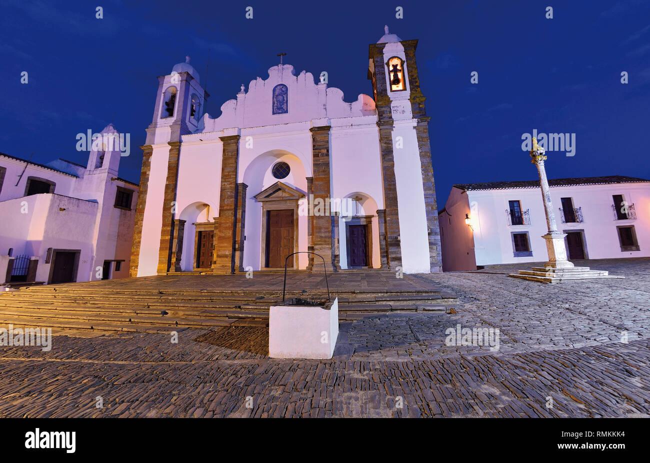Hauptplatz mit mittelalterlichen Kirche, Pranger und historischen, weiß getünchtes Gebäude bei Nacht Stockfoto