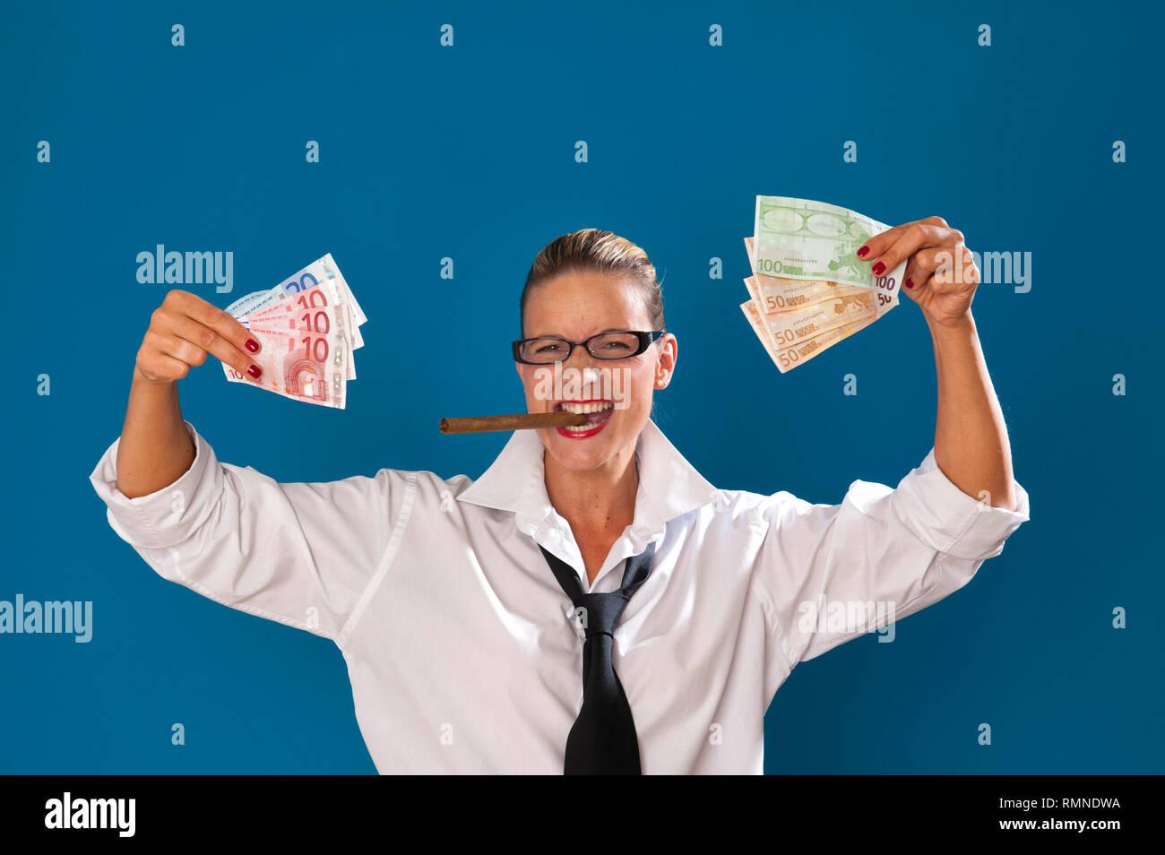 Dunkelblond Frau e Orig. tuerkiser Zauberstab mit strenger Frisur traegt Maennerkleidung, Zigarre im Mund haelt Geldscheine in der Hand HERR: JA PR: JA [ (c Stockbild