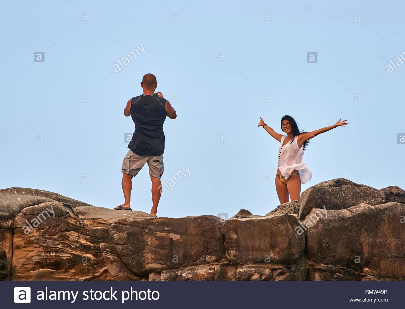 Eine Frau, die auf einem Felsvorsprung - Lächeln und posieren mit ihren ausgestreckten Armen - als Ihr Partner ihr Foto nimmt; mit einem blauen Himmel im Hintergrund. Stockbild