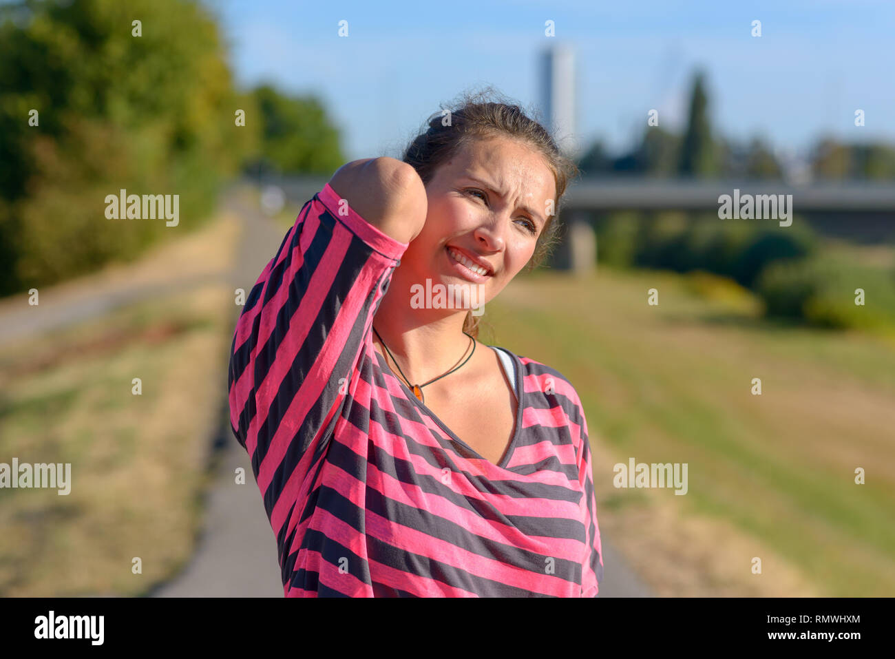 Junge Frau Joggen leidet eine Muskelverletzung stehend hält Hals und unteren zurück, während verzog das Gesicht vor Schmerzen auf der Landstraße, Oberkörper hautnah Stockbild