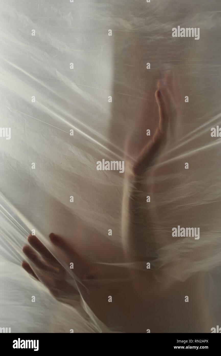 Hände durch die klare Folie. Schöne zarte weibliche Hände. Ein Symbol der illusiveness und Unwirklichkeit. Stockbild