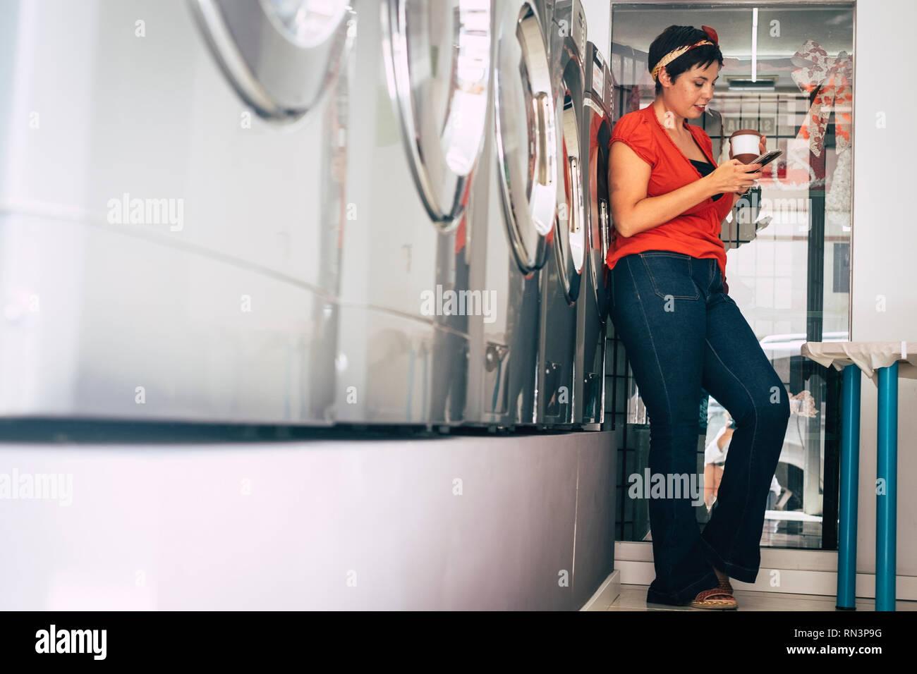 Junge Frau stehen und über Handy, während ihre Kleidung in einer Wäscherei service Shop in der Stadt - moderne Lifestyle zu beschäftigt für Bus gewaschen warten Stockfoto