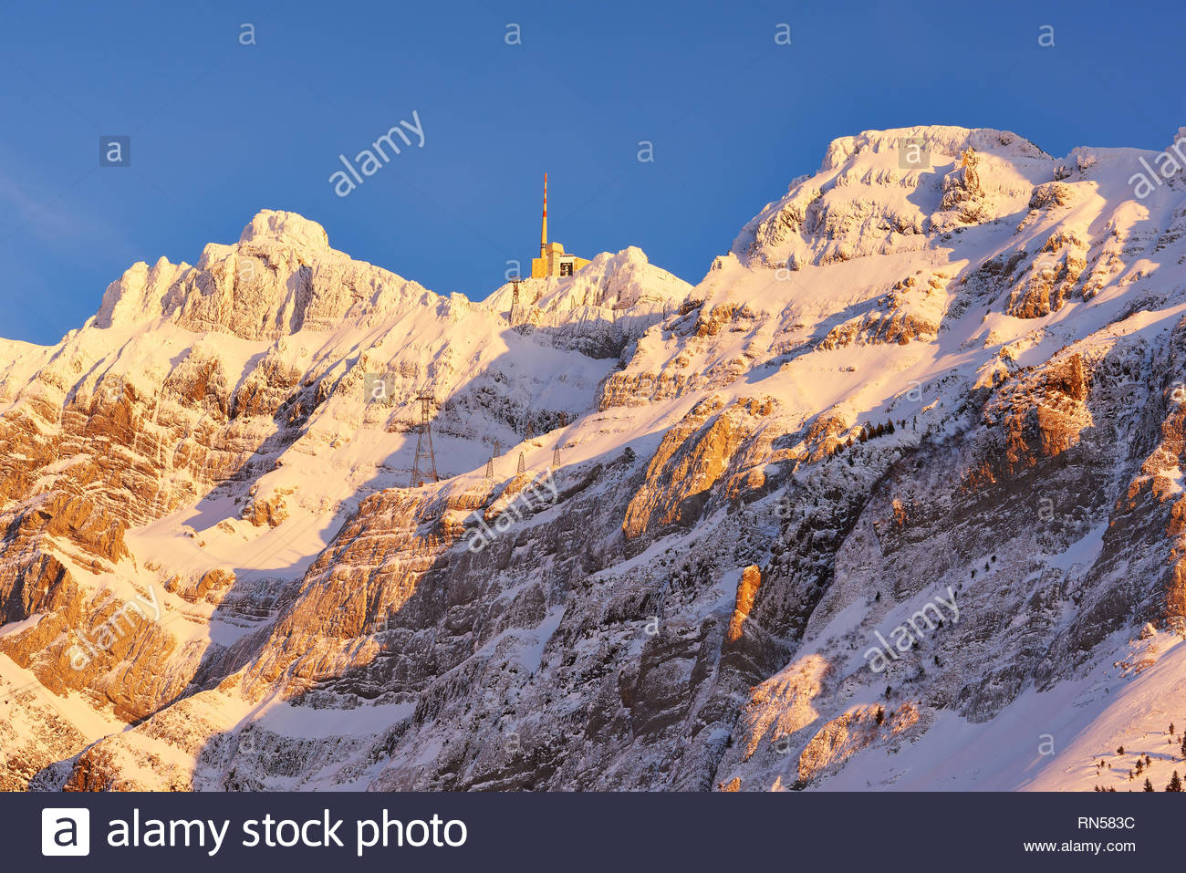 Säntis im Winter Bergstation mit Sendemast, schneebedecktes Felsmassiv im gelben Abendlicht, blauer Himmel, Seilbahnmasten Stockbild