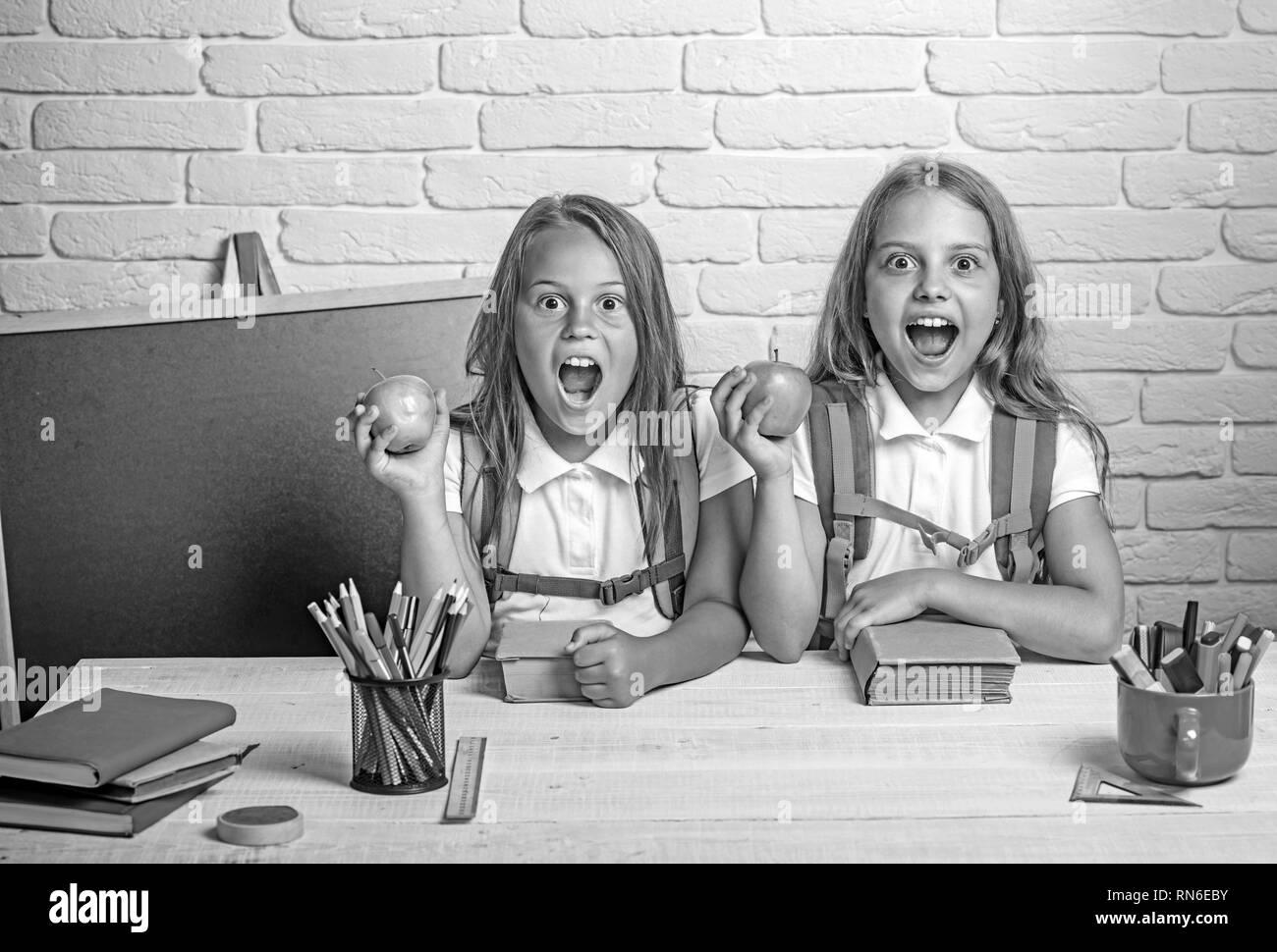 Happy school Zicklein an der Lektion im September 1. Kleine Mädchen essen Apple bei der Mittagspause. Schule der Mädchen. Die Freundschaft der Kleinen Schwestern in Klassenzimmer an Stockbild
