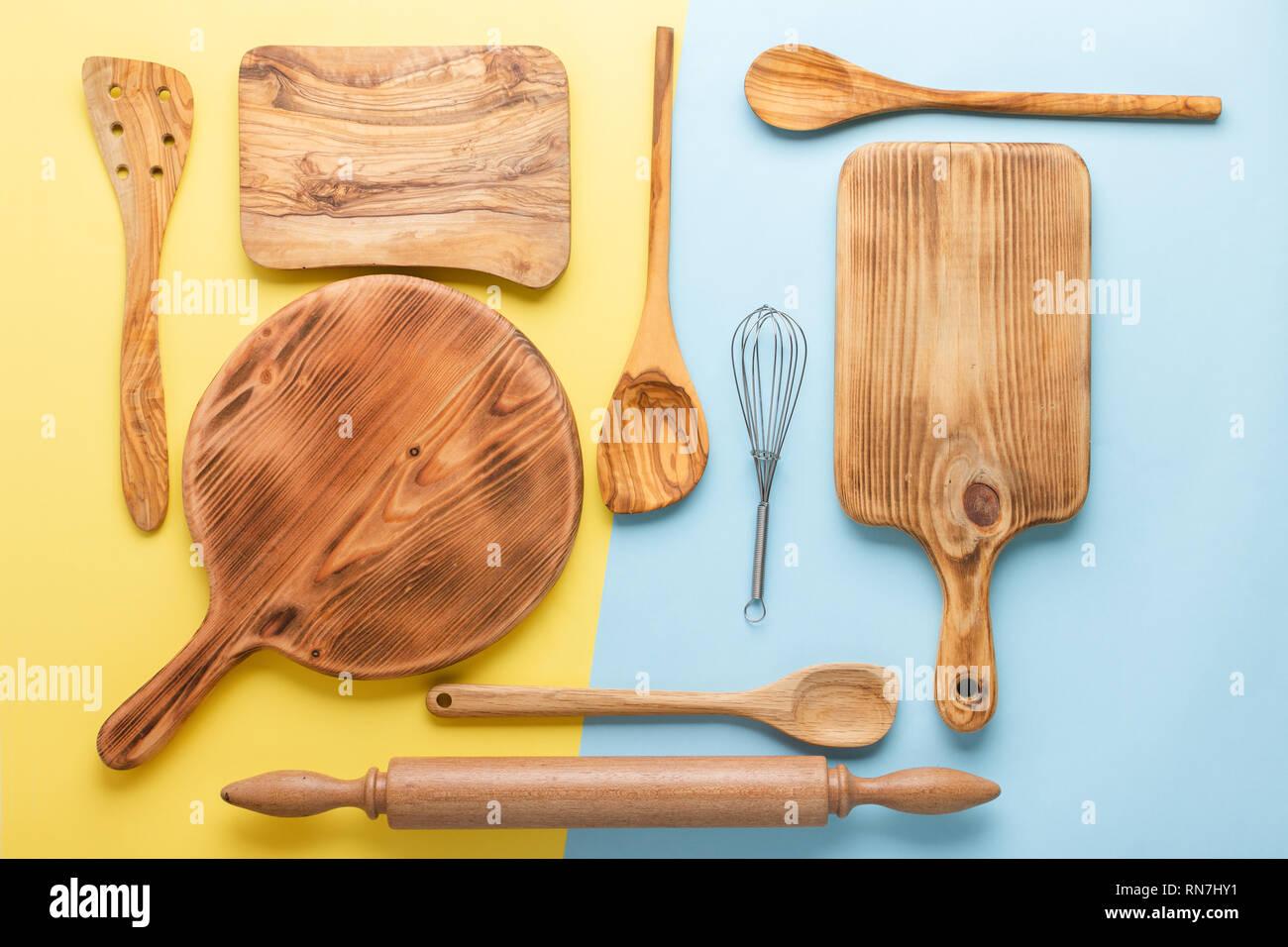 Küchengeräte, Lebensmittelzubereitung kochen accessorises, Schneidebretter, Holzlöffel, Schneebesen auf Blau und Gelb Tabelle, Ansicht von oben, selektiver Fokus Stockfoto