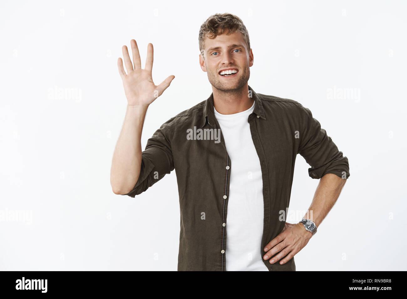 Entspannt und sorglos freundliche junge männliche Sportler Palm heben als geben hohe Fünf- oder Hallo, Gruß mit Hi Geste und Happy Stockbild