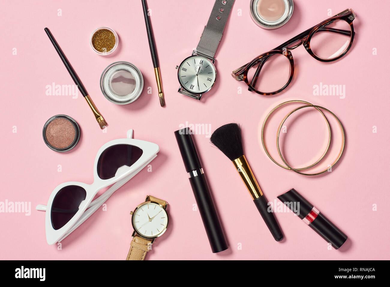 Blick von oben auf die Uhren, Lippenstift, Brillen, Sonnenbrillen, Lidschatten, Rouge, Kosmetikpinsel, Armbänder und Mascara Stockfoto