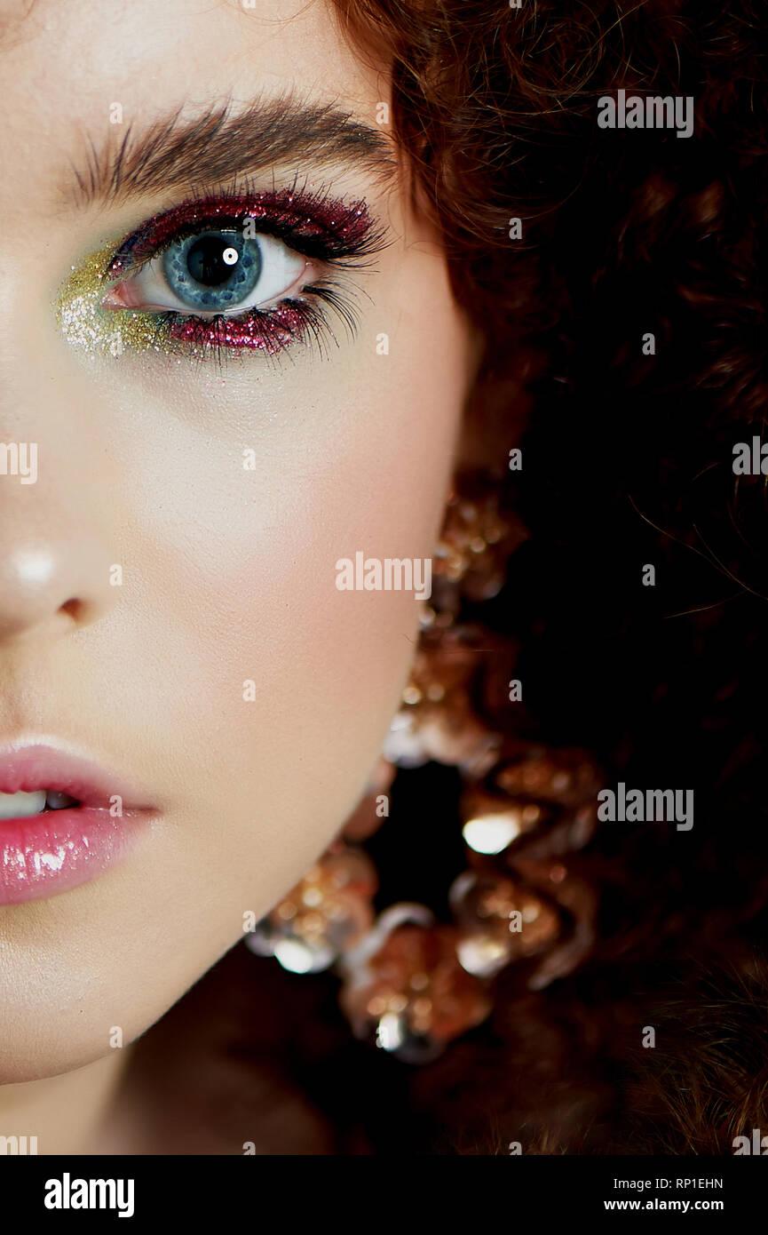Ein Mädchen mit üppigen lockigem rotem Haar. Fast die Hälfte der Fläche mit hellen Make-up und massive Ohrringe. Stockbild