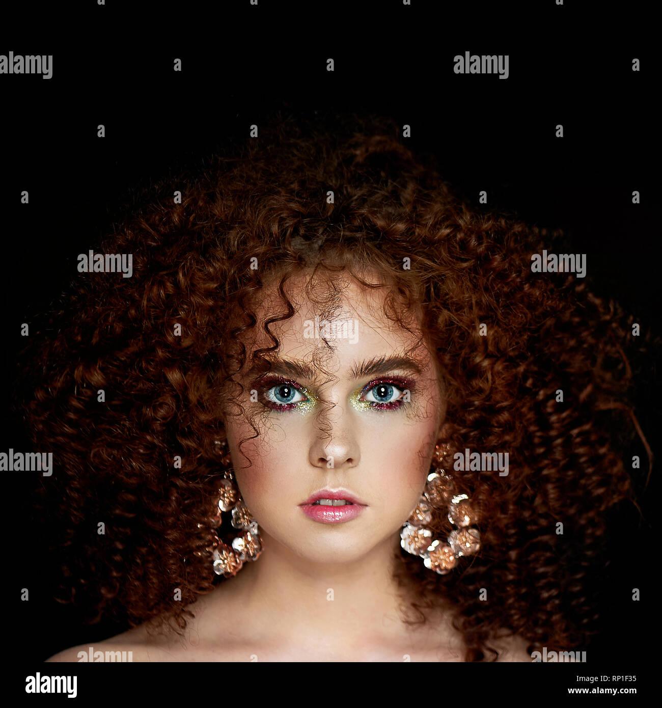 Ein Mädchen mit üppigen lockigem rotem Haar. Schließen Sie das Gesicht mit hellen Make-up und massive Ohrringe. Lila Schatten. Stockbild