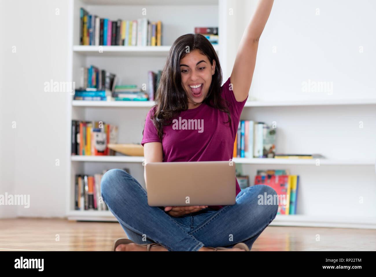 Jubelnde arabische Frau mit Computer innen zu Hause Stockfoto