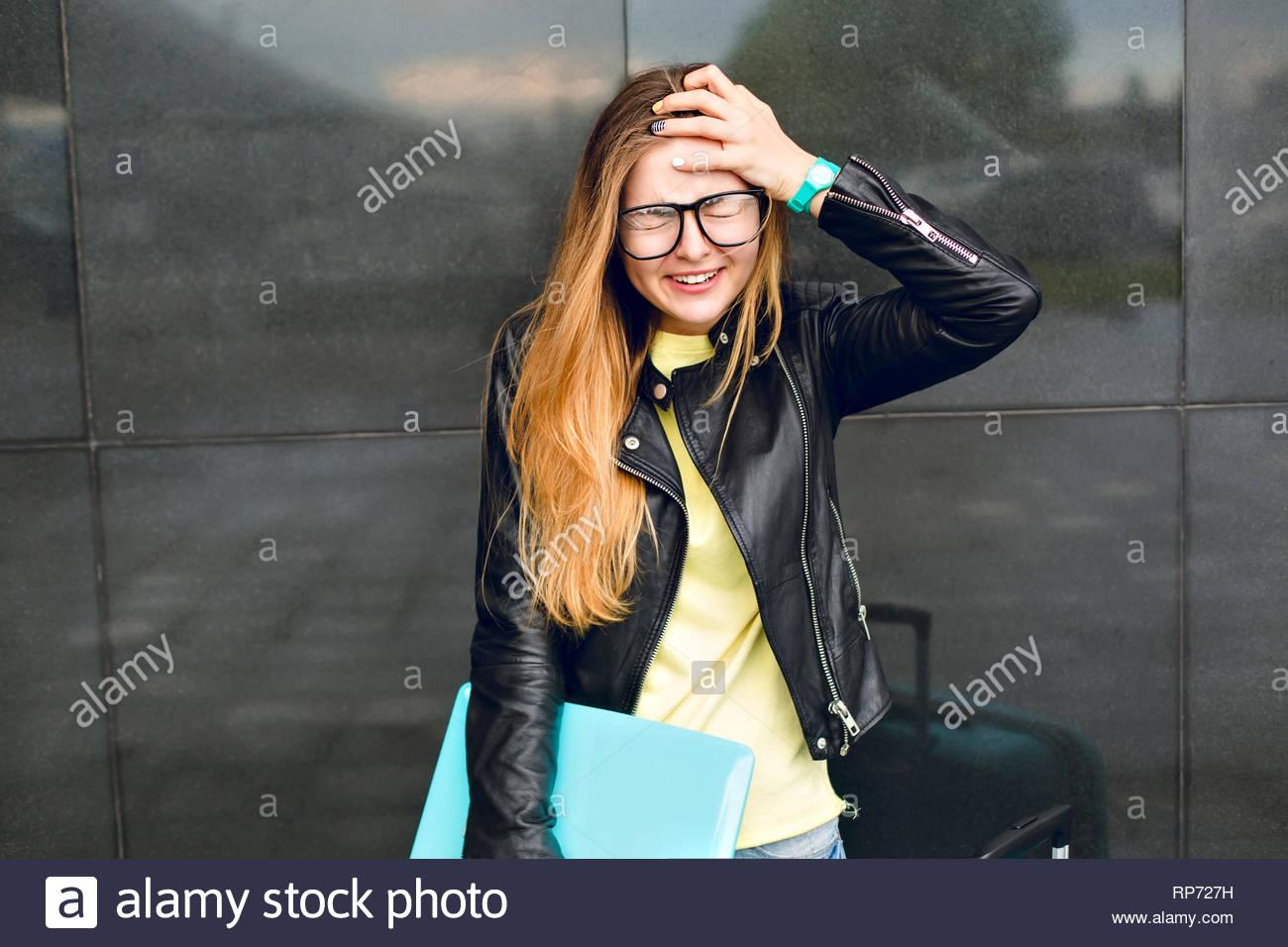 Porträt der jungen Mädchen mit schwarzen Gläsern und lange Haare stehen draußen auf schwarzen Hintergrund. Sie trägt gelb Pullover und schwarze Jacke. Sie sieht Stockbild