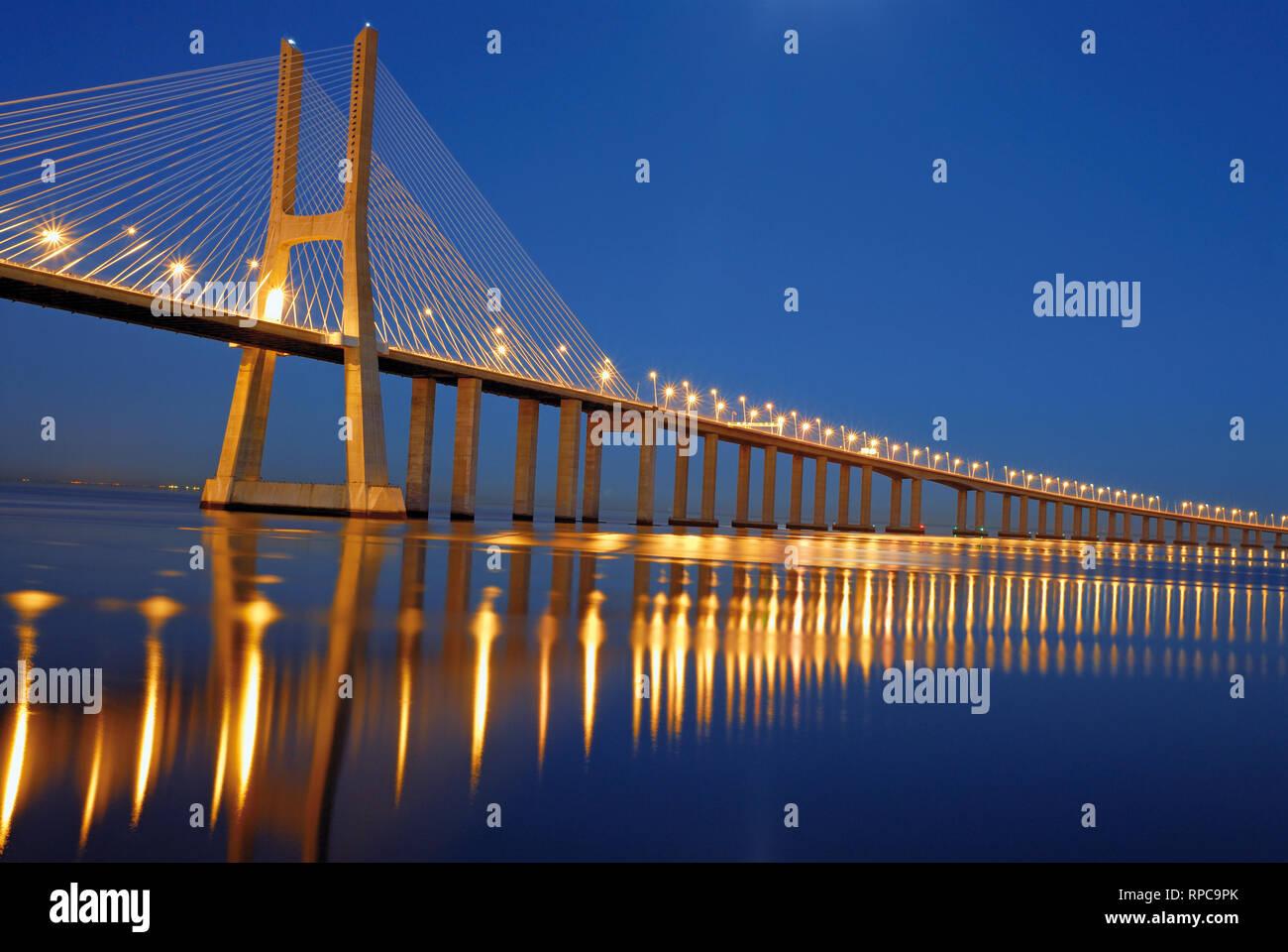 Elegante steel Bridge bei Nacht vorbei an Kilometer über große ruhige Fluss Wasser Stockfoto