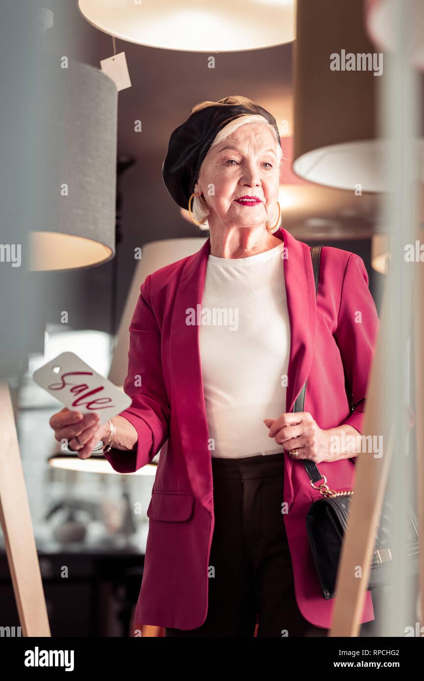 Im Alter von attraktiven fancy Frau mit Verkauf Zeichen in der Hand Stockbild