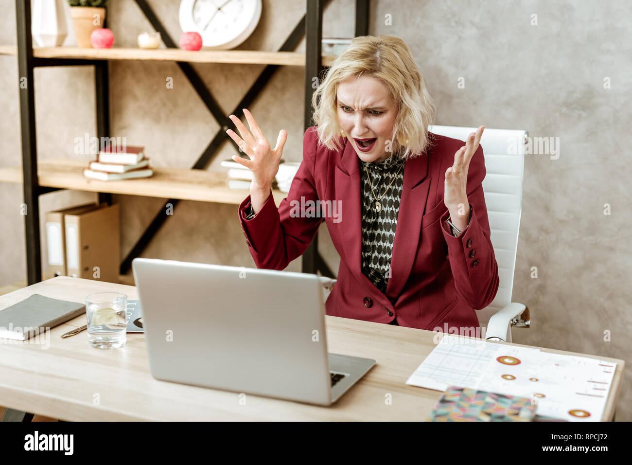 Verrückte wütende Frau schreiend auf Ihrem Laptop während des Angriffs der Aggression Stockbild