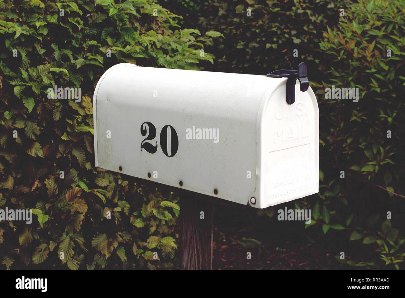 Nahaufnahme von einem weißen Tunnel-Postfach mit der Nummer 20 in Schwarz auf der Seite Stockbild