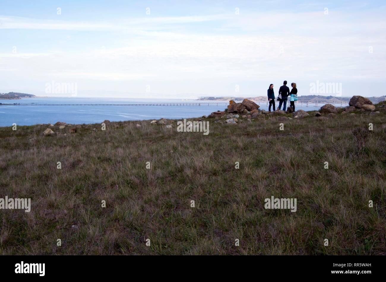 Drei Personen machen Sie eine Pause auf dem Weg nach oben am Berg in Marin County. Sie stoppten die Ansicht der Richmond Brücke zu schätzen. Stockbild