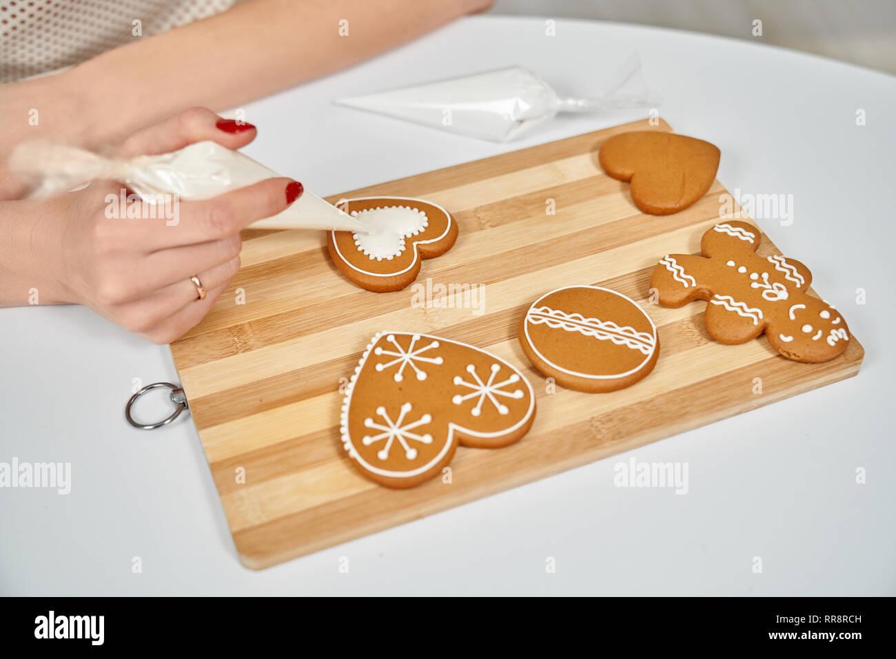 Braune Weihnachtskekse.Weihnachtliche Köstlichkeiten Weibliche Hände Verzieren Braune