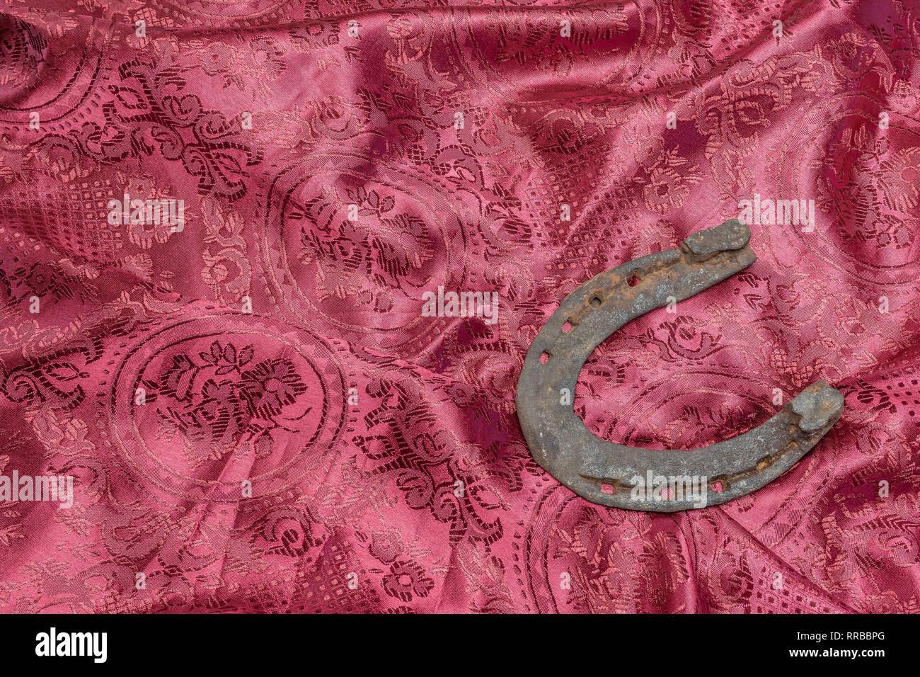 Hufeisen als Symbol für Glück auf einer Seide roter Hintergrund Stockbild