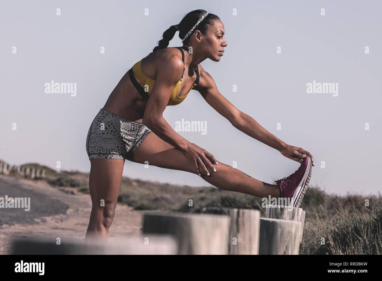 Sportliche schwarze Frau Training am Straßenrand Stockbild
