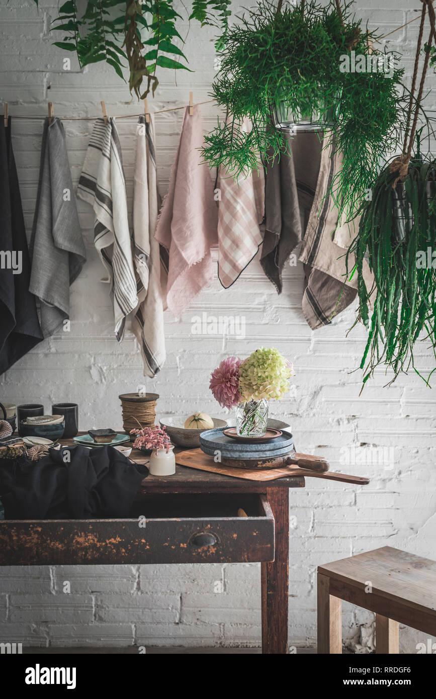 Holztisch mit Haufen frischen rosa Chrysanthemen und weiße Hortensie vase zwischen Pfanne und Küchenutensilien in der Nähe von spüllappen hängen an Twist Stockbild